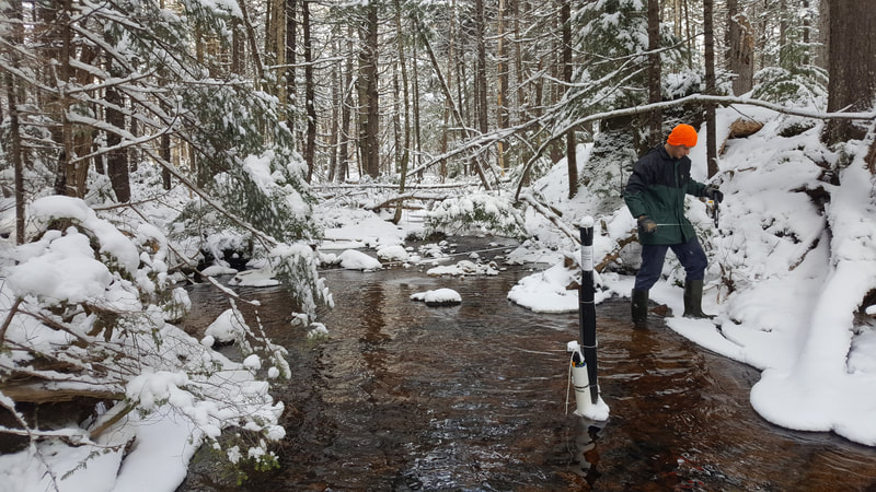 A student taking water samples in a snowy river