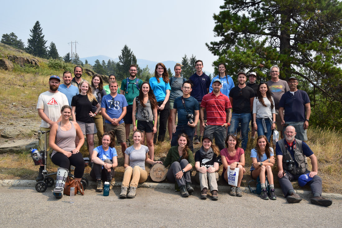 A group of graduate students in front of a forested landscape