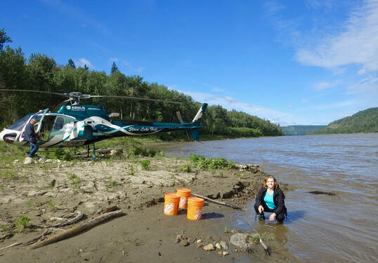 Dr. Monica Emelko samples water at a remote location accessed by helicopter