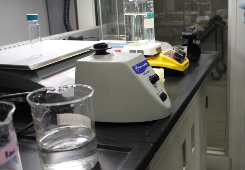 A beaker with water and some water quality equipment
