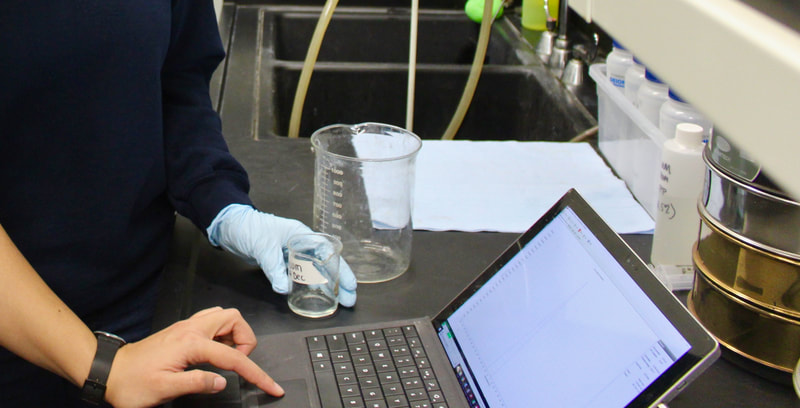 Water in beakers while researchers look at data on a laptop